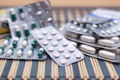 Diversas píldoras y cápsulas en packagings de la ampolla llenadas para arriba en una tabla de cristal imagen de archivo libre de regalías
