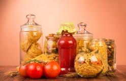 Diversas pastas en tarros, salsa de tomate de la botella, tomate de las formas en marrón Imagen de archivo libre de regalías