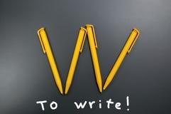 Diversas penas plásticas amarelas sob a forma de uma letra W em um fundo cinzento e nas chamadas a escrever fotografia de stock