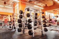 Diversas pesas de gimnasia en gimnasio un interior anaranjado brillante Fotos de archivo