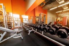 Diversas pesas de gimnasia en gimnasio un interior anaranjado brillante Fotos de archivo libres de regalías