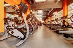 Diversas pesas de gimnasia en gimnasio un interior anaranjado brillante Imagen de archivo