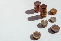 Diversas pilhas das moedas no fundo branco com lugar para seu texto foto de stock royalty free