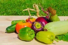 Diversas pimientas, calabacín, tomates, pepinos, cebollas, maíz en un tablero de madera en el fondo de la hierba Foto de archivo