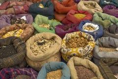 Diversas semillas vegetales en bolsos multicolores en el mercado foto de archivo