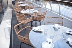 Diversas tabelas do vidro com cadeiras de madeira aprontam-se preparado para o almoço Imagem de Stock