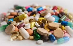 Diversas tabletas, c?psulas, drogas de la terapia y p?ldoras multicoloras farmac?uticas con el fondo brillante imágenes de archivo libres de regalías