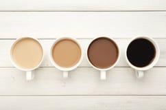 Diversas tazas de café en la madera blanca, visión superior Fotografía de archivo