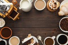 Diversas tazas de café y pasteles dulces en la tabla de madera del vintage, a Fotografía de archivo libre de regalías