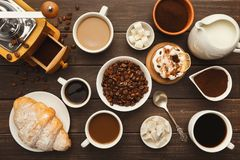 Diversas tazas de café y pasteles dulces en la tabla de madera del vintage, visión superior Imagen de archivo libre de regalías