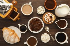 Diversas tazas de café y pasteles dulces en la tabla de madera del vintage, visión superior Fotos de archivo