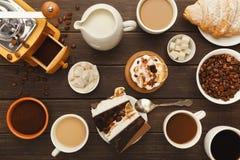 Diversas tazas de café y pasteles dulces en la tabla de madera del vintage, visión superior Fotos de archivo libres de regalías