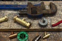 Diversas válvulas y llaves en un banco de trabajo de los fontaneros Imagen de archivo libre de regalías