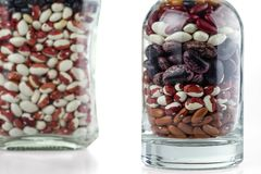 Diversas variedades de habas de riñón en las botellas de cristal aisladas en el fondo blanco foto de archivo