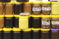 Diversas variedades de miel en los bancos, ofrecidas para la venta en la f Fotos de archivo libres de regalías