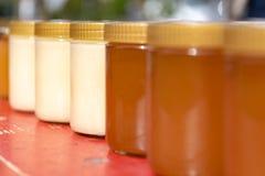 Diversas variedades de miel de las abejas en botella en pequeños tarros imagenes de archivo