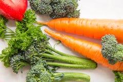 Diversas verduras e hierbas frescas con los waterdrops en la tabla blanca, composición auténtica vegetariana fotografía de archivo libre de regalías