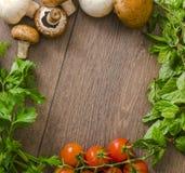 Diversas verduras en un círculo en el piso de madera Imagen de archivo