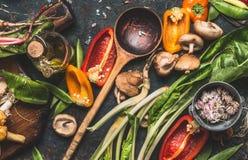Diversas verduras frescas con la cuchara de cocinar de madera para la consumición y la nutrición sanas en fondo rústico oscuro Imagen de archivo
