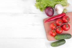 diversas verduras incluyendo, tomates, pimientas, pepinos, cebollas, ajo y lechuga en un fondo de madera blanco Visión superior imagen de archivo libre de regalías