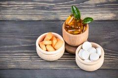Diverse alternatieve en homeopatic pillen in houten containers Stock Foto