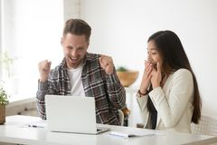 Diverse amazed colleagues excited by online win or result achiev. Ement, asian businesswoman and caucasian businessman celebrating team victory looking at laptop Royalty Free Stock Photography
