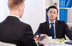 Diverse arbeiders tijdens lunchtijd in bureau Stock Fotografie