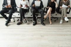 Diverse bedrijfsmensen die in rijholding smartphones wachten en Stock Foto's
