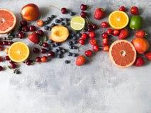 Diverse bessen en vruchten op een grijze achtergrond Aardbeien, kersen, sinaasappel, perzik, bosbessen, kalk, grapefruit royalty-vrije stock fotografie