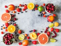 Diverse bessen en vruchten op een grijze achtergrond Aardbeien, kersen, sinaasappel, perzik, bosbessen, kalk, grapefruit stock foto's