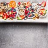 Diverse bessen met muesli, noten en haver voor ontbijtontbijt in kruiken stock afbeelding
