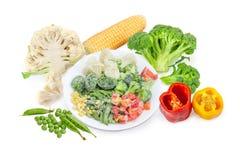 Diverse bevroren en verse groenten op een witte achtergrond Stock Foto's