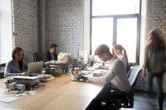 Diverse bezige medewerkers die zitting werken bij gedeeld bureau stock fotografie