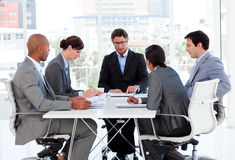 A diverse business group discussing a budget plan. In a meeting