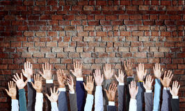 Diverse Business Hands Raised on Brick Wall Royalty Free Stock Image