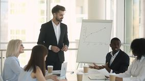 Diverse business partners negotiating during meeting in board room. Caucasian coach skilled trainer or company boss talking with diverse members at briefing in stock video footage