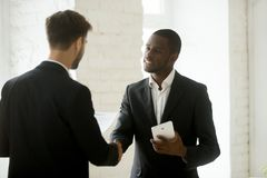 Diverse business partners shaking hands standing with contract a. Diverse business partners in suits shaking hands standing in office, smiling african american Stock Photos