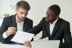 Diverse business partners in suits holding documents discussing Stock Photo
