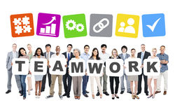 Diverse Business People Holding Word Teamwork. Multi-Ethnic Group Of Diverse People Holding Letters That Form Teamwork And Related Symbols Above stock photography