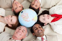 A diverse business people lying around a globe. A diverse business people lying on the floor around a globe Royalty Free Stock Image