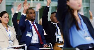 Business people raising their hands in a business seminar 4k. Diverse Business people raising their hands in a business seminar. They are attending a seminar 4k stock video footage