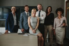 Diverse business professionals together in meeting room. Portrait of diverse business professionals together in office meeting room. Team of corporate stock photos