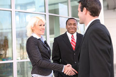 Diverse business team. Three friendly businesspeople shaking hands outside office building royalty free stock image