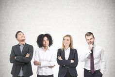 Diverse business team brainstorming, concrete. Members of a diverse business team brainstorming standing near a concrete wall. Concept of a team work and success Stock Photos