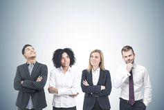 Diverse business team brainstorming, gray. Members of a diverse business team brainstorming standing near a gray wall. Concept of a team work and success. Mock Royalty Free Stock Image