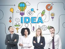Diverse business team brainstorming, idea. Members of a diverse business team brainstorming standing near a gray wall with a bright idea sketch drawn on it Stock Images