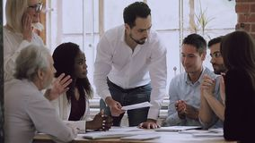 Diverse business team brainstorming on paperwork talking laughing at meeting