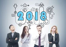 Diverse business team brainstorming, 2018 start up. Members of a diverse business team brainstorming standing near a gray wall with a 2018 business plan sketch Royalty Free Stock Image