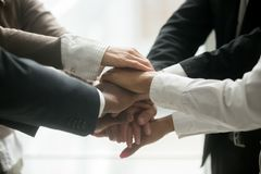 Diverse business team holding pile of hands promising loyalty, c. Diverse multiracial business team holding stacked pile of hands together promising help loyalty stock photography