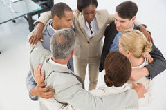 Diverse business team hugging in a circle Stock Images
